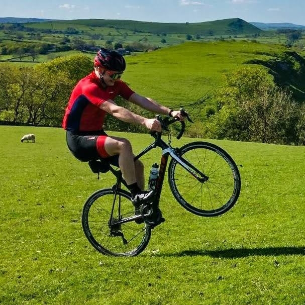 Ben doing a wheelie on a bicycle in a field